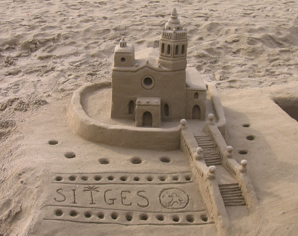 A sandcastle on the beach in Sitges, Spain by Jef Nickerson