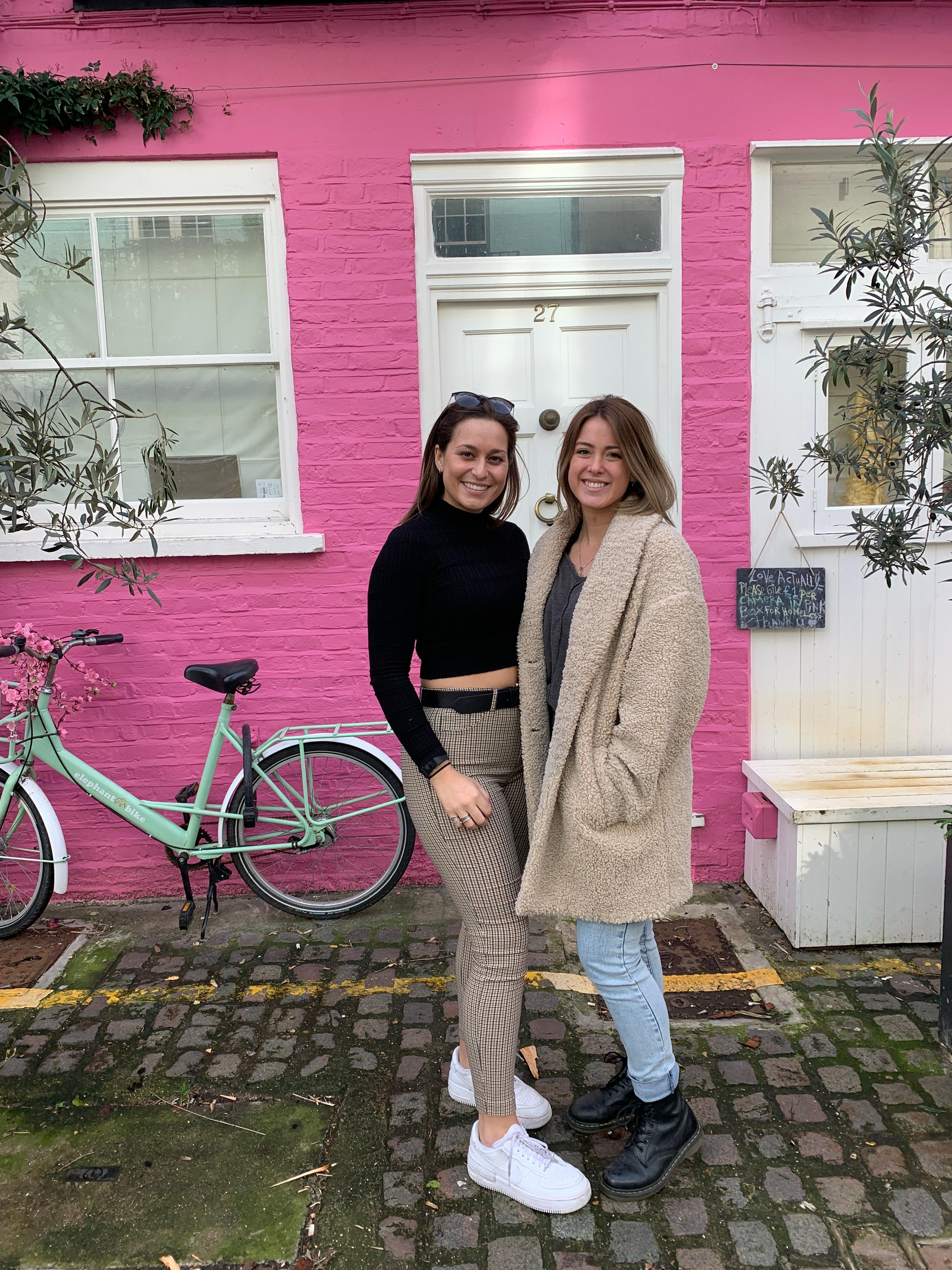 Photo with a friend in front of a pink wall in London