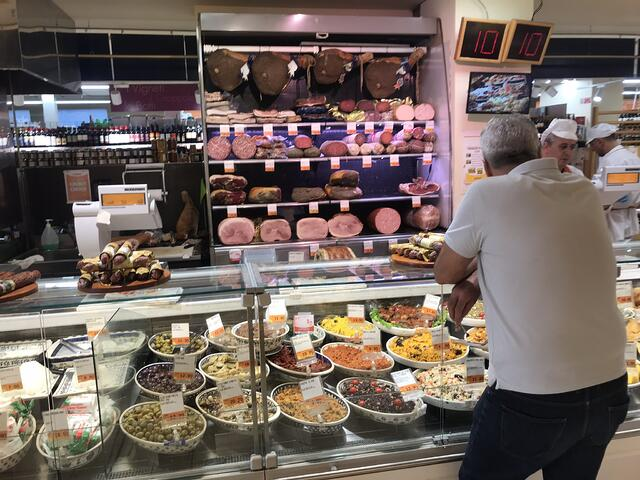 Picture of people ordering at a deli counter in a grocery store