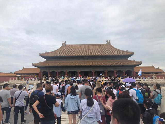 A crowd of people tour the Forbidden City